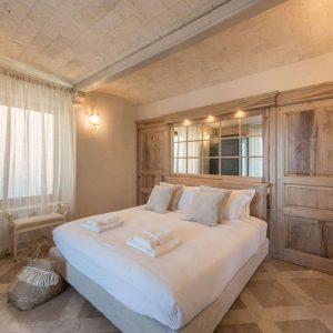 Camera matrimoniale dal design classico, realizzata con materiali naturali di pregio