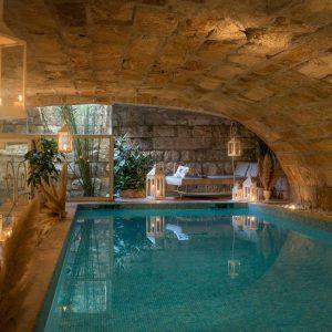 Крытый бассейн с подогревом из натурального камня, предназначенный для релаксации и хорошего самочувствия.